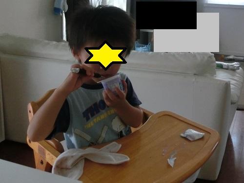 木製のダイニング子供用いすでヨーグルトを食べている3歳男の子