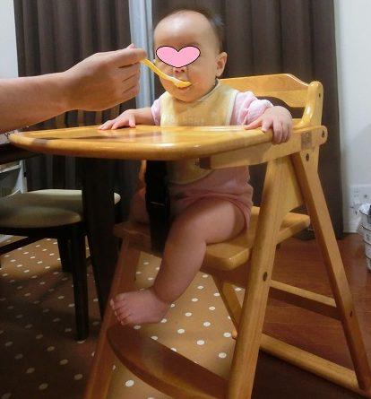 木製の子供用ベビーチェアで離乳食を食べている赤ちゃん