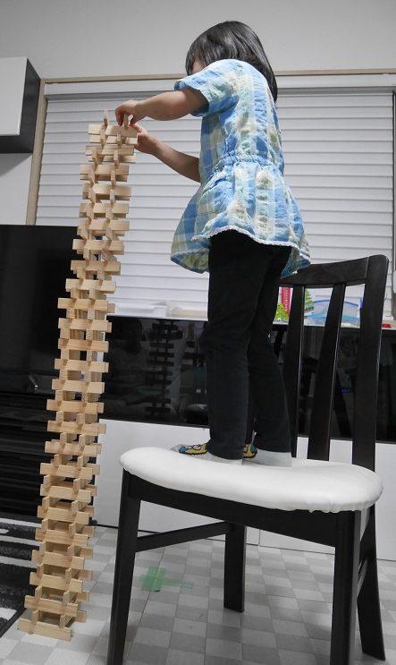 椅子の上にのぼってカプラを積み上げる5歳の女の子