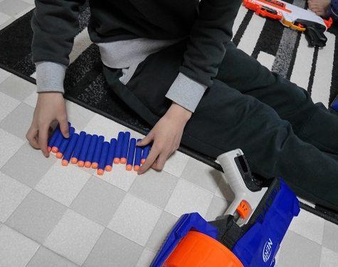 ナーフ銃の弾を集めている小学生男の子