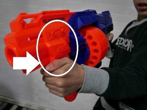 ナーフ銃のレバーを引く小学生男の子