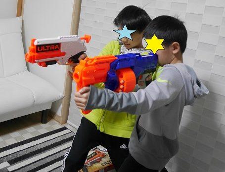 ナーフ銃のウルトラシリーズとエリートシリーズで的当てを競争している兄弟