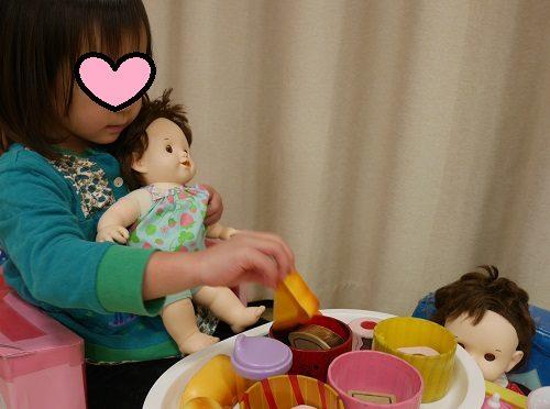 ぽぽちゃん人形にご飯をあげている3歳の女の子