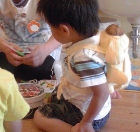 人形をおんぶしている2歳の男の子
