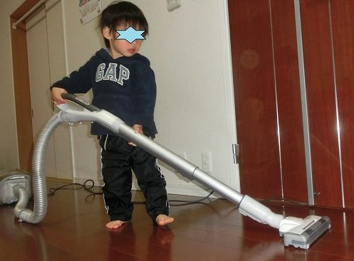 ママの真似をして掃除機をかけている3歳男の子