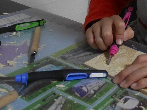 彫刻刀で木の板を彫っている小学生