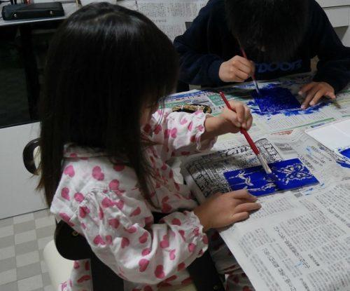 版画で板にインクを塗っている4歳女の子