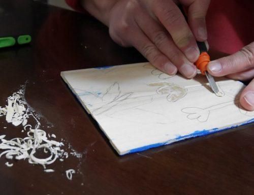 ベニヤ板に彫刻刀で版画の絵を彫っている手