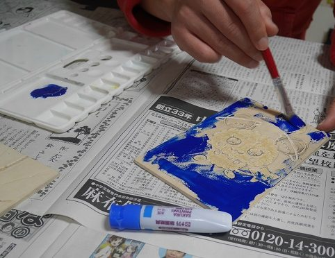 版画で筆を使って木にインクを塗っている子供