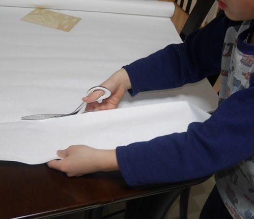 版画の準備として版画紙を切っている小学生