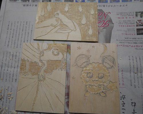 ベニヤ板に版画用のイラストを彫っている