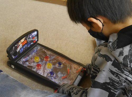 パチンコのピンボールおもちゃで遊んでいる小学生男の子