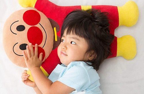 アンパンマンの枕で寝る女の子