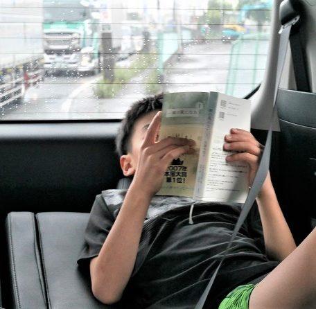 家族でお出かけしている車の中で、「一瞬の風になれ」を夢中で読む小学生の男の子