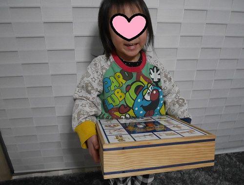 カプラ100ピースの箱を持っている3歳女の子