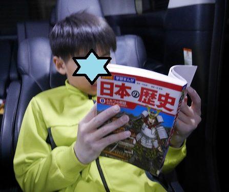 車の中で、講談社の日本の歴史を読んでいる小学生の男の子
