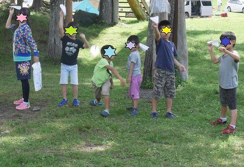 小学生の子供が紙ヒコーキ競争をしているところ