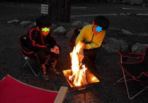 小学校高学年男子がキャンプで焚火を見つめているところ