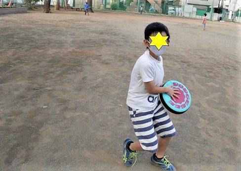 ラングスジャパンのドッヂビーで公園で遊んでいる小学生の男の子