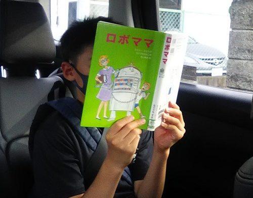 車の中で「ロボママ」を読む小学生男子