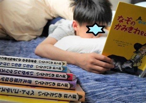 ぼくはめいたんていシリーズの本を、ベッドの中で読む小学生の男の子