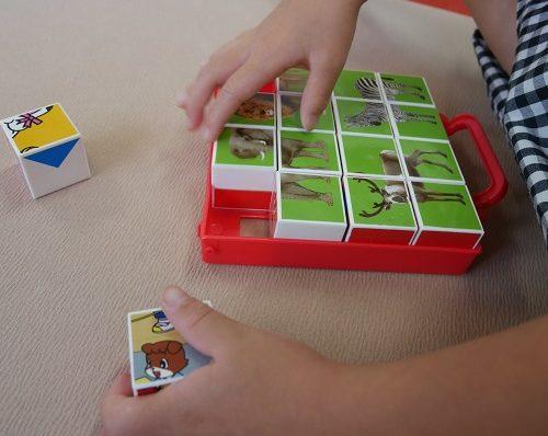絵合わせキューブパズルをしている5歳の女の子