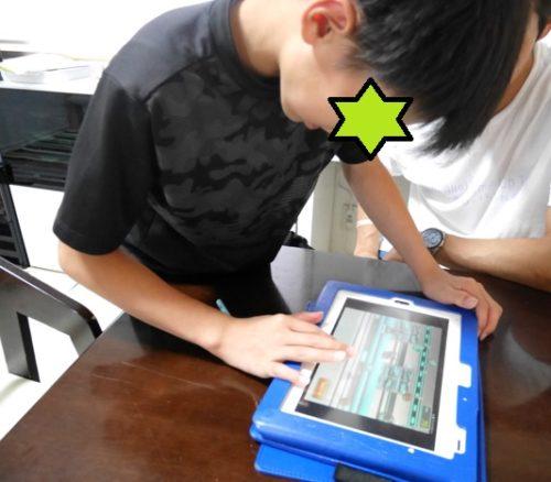 チャレンジタッチのゲームを夢中でやっている小学生の男の子