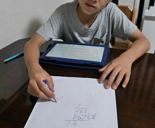 タブレットでRISUの問題を解きながら紙にひっ算をしている男の子