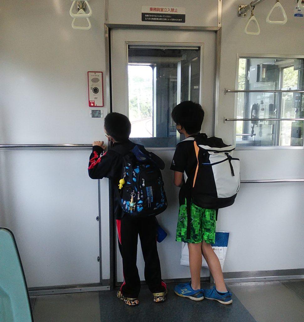 社会科見学や習い事でリュックサックを背負って電車に乗る小学生男子